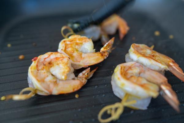 Krewetki smażymy lub grillujemy z dwóch stron, smarujemy delikatnie dresingiem, warzywa mieszamy z pozostałą ilością.