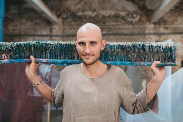 Kuba Mach do malowania wykorzystuje ogromne miotły, ale też dłonie czy nawet całe ciało.