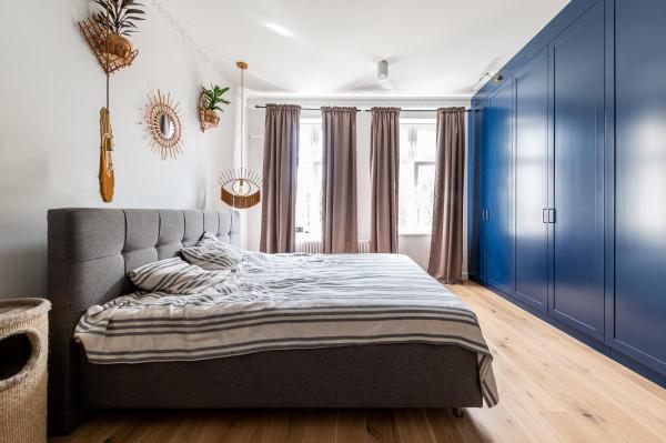 Stonowane wnętrze sypialni dopełnia duża zabudowa meblowa w kolorze kobaltowym.