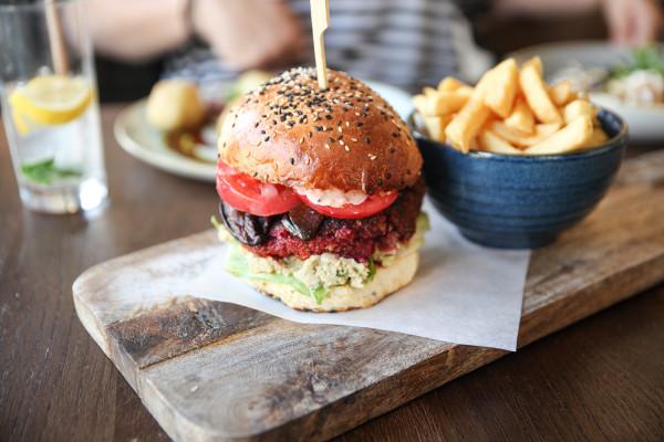 """W kolejnym odcinku cyklu """"Jemy na mieście"""" odwiedziłam restaurację Spożywczy na Dolnym Mieście. Na zdjęciu: beetroot, czyli wegański burger z burakiem, guacamole, """"boczkiem"""" z bakłażana i frytami."""
