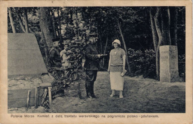 Przedwojenna karta pocztowa przedstawiająca przejście piesze w Kolibkach - polski policjant sprawdza dokumenty turystki, a za nim stoi gdański strażnik.