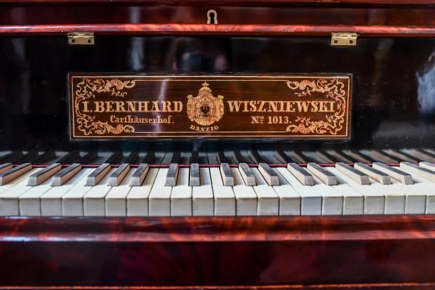 Zdjęcie przedstawia klawiaturę najstarszego gdańskiego fortepianu z około 1830 roku. Nad klawiaturą znajduje się tabliczka znamionowa firmy Wiszniewskich w języku niemieckim: I. Bernhardt Wiszniewski, Carthauserhof, no 1013.
