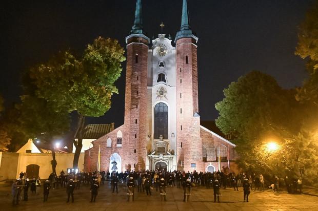 Kordon policji przed Katedrą Oliwską czeka na protestujący tłum.