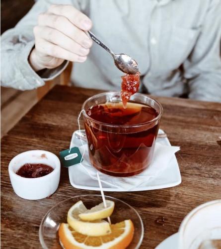 Gorąca herbata z konfiturą z wiśni i cytryną.