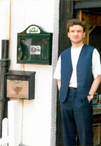 Dariusz Knyszyński, pierwszy barman Błękitnego Pudla. Zdjęcie na tle wejścia do lokalu, początek drugiej połowy lat 90.