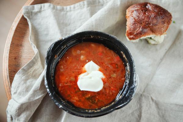 Barszcz ukraiński z mięsem, śmietaną i bułeczką od restauracji Pan Kotowski.