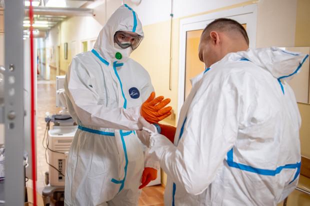 Kontakt z pacjentem poprzedzają żmudne i drobiazgowe przygotowania - pracownicy szpitala muszą się dokładnie zabezpieczyć, żeby zminimalizować ryzyko zakażenia koronawirusem.