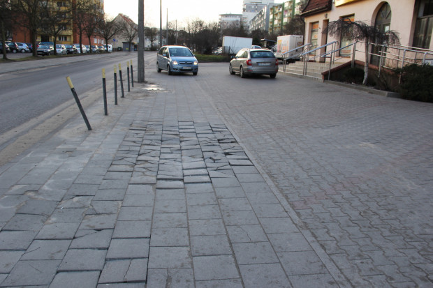 Regularnie naprawiany chodnik jest nieustannie niszczony przez auta, które wjeżdżają na miejsca postojowe zlokalizowane przed stojącymi przy ul. Słowackiego pawilonami.