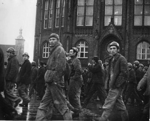 Robotnicy wracający do Stoczni Gdańskiej im. Lenina po pierwszych protestach pod Komitetem Wojewódzkim PZPR, w tle kościół św. Jakuba i I Liceum Ogólnokształcące. 14 grudnia 1970 r.