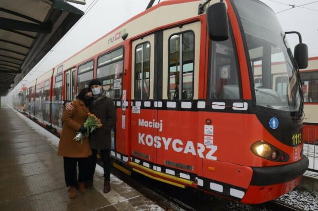 Hanna Kosycarz i Konrad Kosycarz, żona i syn Macieja, na tle tramwaju, który został oklejony reprodukcjami zdjęć dwóch słynnych gdańskich fotoreporterów.