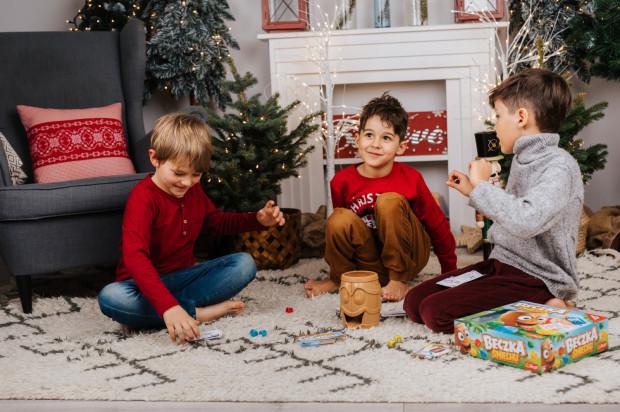 Planszówki to jeden z najlepszych pomysłów na spędzanie razem czasu. Na zdjęciu chłopcy grają w grę Beczka śmiechu.