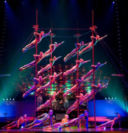 """Podczas jednego z numerów kolorowe istoty wspinają się na siedmiometrowe chińskie tyczki i poruszają się po nich z dziecinną łatwością. Chińskie tyczki w """"Saltimbanco"""" symbolizują drapacze chmur. Szkoda, że nasze wieżowce nie są tak ciekawe."""