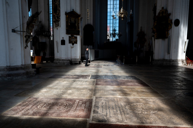 W posadzce Bazyliki Mariackiej znajduje się kilkaset płyt nagrobnych. Większość płyt pochodzi z XVII i XVIII stulecia. Najstarsza z nich pochodzi z 1411 r. i została wykonana jako oznaczenie miejsca pochówku burmistrza Konrada Leczkowa, podstępnie zamordowanego przez Krzyżaków.