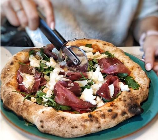 Pizzę neapolitańską najlepiej podzielić na cztery kawałki, a następnie jeść sztućcami, zaczynając od jej cienkiego środka.