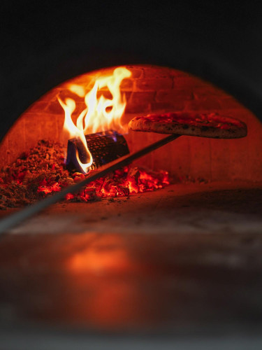 Pizza wypiekana jest w piecu opalanym drewnem, który rozgrzewa się do niemal 500 stopni Celsjusza.