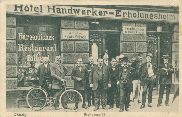 Rowerzysta wśród grupy mężczyzn przed hotelem dla rzemieślników na ul. Szerokiej, początek XX w.