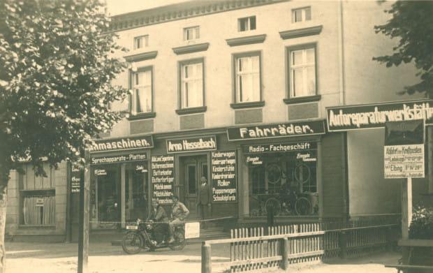 Sklep i warsztat należący do Arno Hesselbacha, najpewniej w Nowym Dworze Gdańskim (właściciel posiadał też sklep na ul. Grobli III w Gdańsku), koniec lat 20. Sprzedawał i naprawiał m.in. rowery oraz radia.