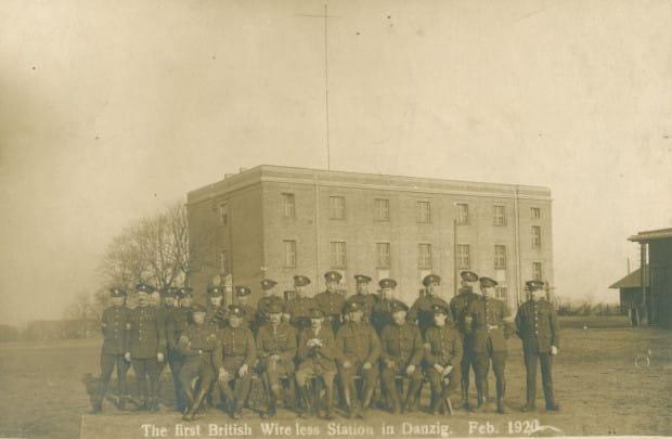 Unikatowa fotografia prezentująca załogę angielskiej wojskowej stacji radiowej na Górze Gradowej, 1920 r. Radiostacja mieściła się w Nowych Koszarach widocznych w tle. Obecnie to budynek przy ul. Gradowej 11.