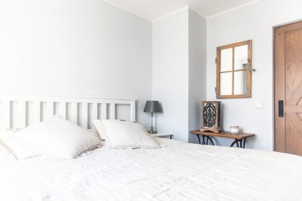 Bardzo ważnym elementem sypialni jest postarzane lustro, które kiedyś było elementem budynku, w którym obecnie pracują właściciele.
