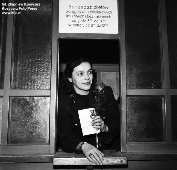 Marzec 1962 r. Kasjerka w okienku komunikacyjnej kasy biletowej z goździkiem w ręku.
