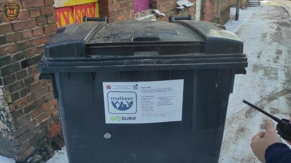 Mężczyzna w dużym kontenerze na śmieci przewoził kuchenkę gazową na złom.