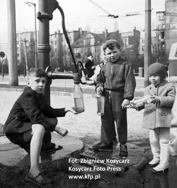 Dzieci przy pompie na rogu skweru Kościuszki i ul. Świętojańskiej napełniają wodą butelki na śmigus-dyngus. 1959 rok.