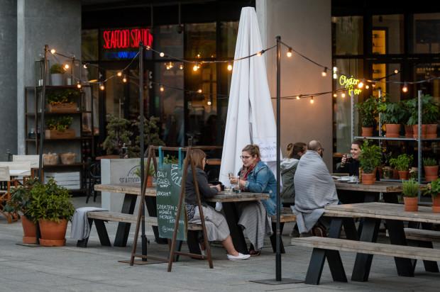 To zdjęcie zostało wykonane przed wprowadzeniem obowiązujących obostrzeń. Obecnie restauracje mają zakaz obsługiwania gości w ogródkach, ale nie mogą im zabronić korzystania z rozstawionych stołów i krzeseł. A ci chętnie je zajmują, bo wygodniej jeść - nawet posiłek na wynos - na siedząco niż na stojąco.