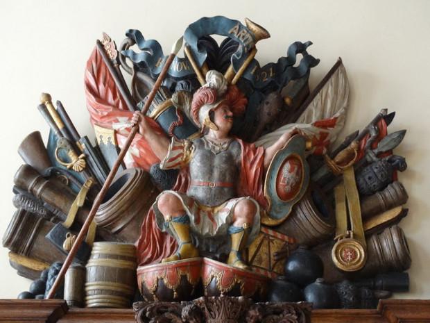 Bóg wojny - Ares lub Mars - w otoczeniu uzbrojenia z początków XVIII wieku. Takie panoplium zdobi jedną ze ścian Sieni Gdańskiej w Dworze Artusa.