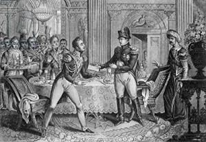 """Cesarz Napoleon wręcza swojemu marszałkowi Pierre'owi Lefebvre, świeżo mianowanemu księciu Gdańska, """"blok gdańskiej czekolady"""" w podziękowaniu za zdobycie miasta."""