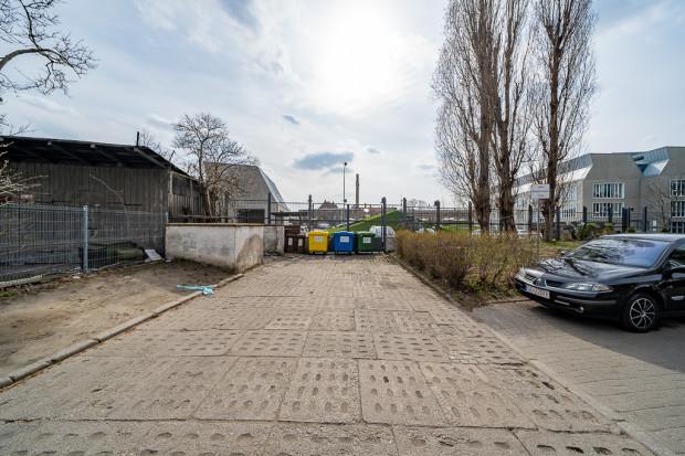 Efekt zapisów planu zagospodarowania dla terenów LPP - na przedłużeniu ul. Królikarnia postawiono płot i śmietniki, choć linie zabudowy miały umożliwić realizację przejścia.