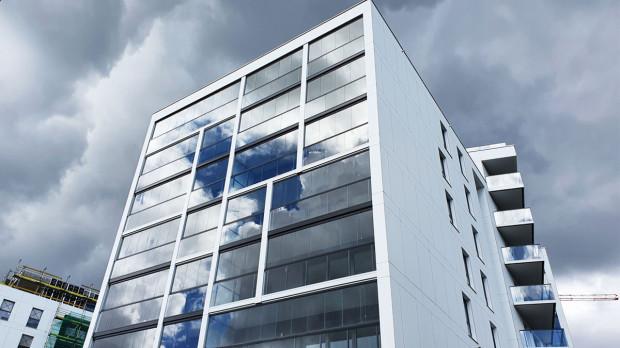 Duże przeszklenia, w tym szklane przesłony balkonów, stały się ekranem, który odbija niebo i otoczenie.