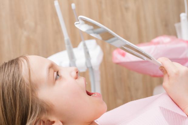 """Przygotowując dziecko do wizyty u stomatologa, lepiej unikać sformułowań, które mogą mu sugerować, że będzie odczuwać ból, jak np.: """"Nie bój się"""" """"czy """"Nic nie będzie bolało""""."""