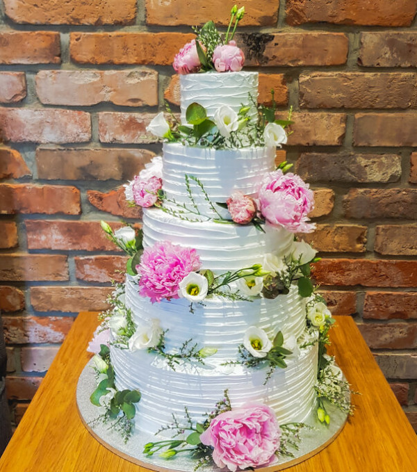 Romantyczny biały tort z trójwymiarową dekoracją kwiatową. Świeże kwiaty stanowią idealne uzupełnienie eleganckiego wypieku.