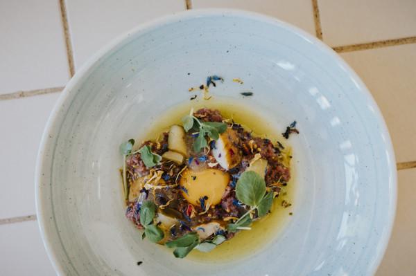 Przystawka mięsna: tatar z bawety wołowej, kiszony ogórek, marynowane grzyby i chrust ziemniaczany.
