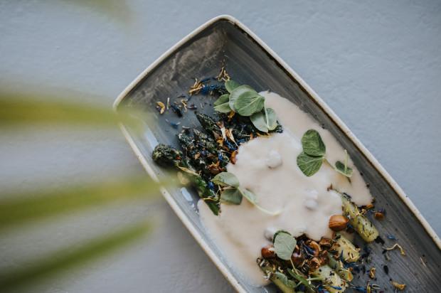 Przystawka roślinna: zielone szparagi, sos jabłkowy, orzechy laskowe i chips z ziemniaka.