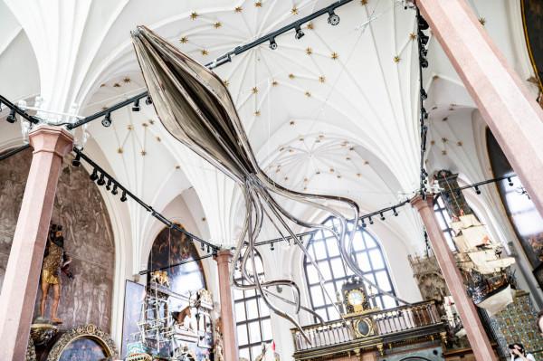 Prawie 13 metrów długości i 250 kilogramów stali niemalże na wyciągnięcie ręki zwiedzającego. W odbiciu rzeźby znajdą się Wielki Piec, malowidła oraz historyczne modele okrętów z Wielkiej Hali Dworu Artusa.