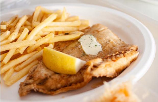 """Ryba z frytkami, znana jest także jako """"fish & chips""""  - brytyjskie danie ze smażonej ryby, skropione octem, całość tradycyjnie zawinięta w gazetę."""