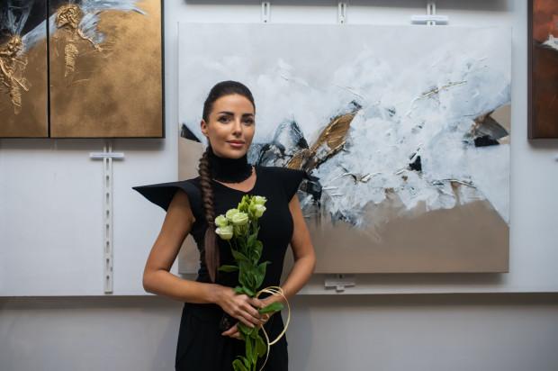 Alicja Domańska na tle obrazów swojego autorstwa.