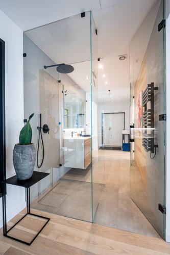 Centralnym pomieszczeniem w mieszkaniu jest przechodnia łazienka, która została oddzielona ścianami z aktywnego szkła.