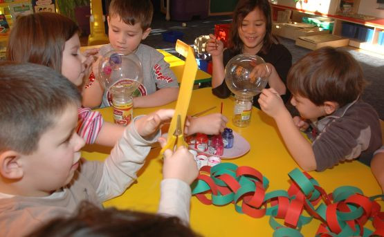 Przedszkolaki przygotowują ozdoby choinkowe.