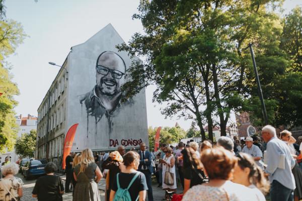 Odsłonięcie muralu Pawła Adamowicza. Na zdjęciu widać, że tylko ściana szczytowa jest wyremontowana. Od frontu budynek wciąż ma zniszczoną elewację.