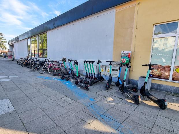 Istniejące stojaki rowerowe i parking dla hulajnóg tuż przy ścianie dworca.