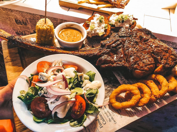 Stek Tomahawk jest wykrawany ze środkowej części antrykotu. To długi mięsień biegnący wzdłuż kręgosłupa, przyrastający do kręgów piersiowych oraz do żeber. Mięso z tej części wołu ma delikatne włókna oraz wyróżnia się marmurkowatością, która wzbogaca jego soczystość. Idealna propozycja na kolację czy obiad.