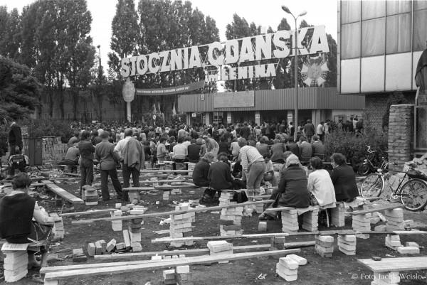 Zdjęcie historyczne, przedstawiające ławki ustawione przez studentów przed Bramą nr 2 w sierpniu '80.