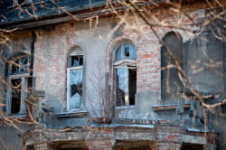 balkon jest już prawie bez balustrady, okna nie mają szyb, choć widać w niektórych resztki drewnianych żaluzji...