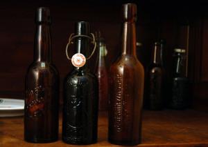 """Butelki z browaru Richarda Fischera z Nowego Portu. Najbardziej popularna, zielona, przez kolekcjonerów nazywana jest """"butelką z ludzikiem""""."""