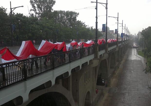 Na 2 godz. przed meczem, w Warszawie doszło do oberwania chmury. Kibice chronili się pod długimi polskimi flagami.