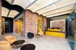Recepcja. Surowe ceglany ściany skontrastowane z podświetlanym sufitem i bursztynowymi elementami wykończenia.