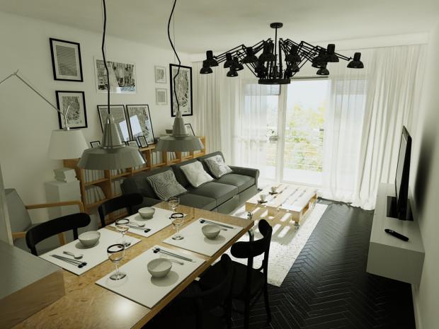 Bejcowana na czarno drewniana podłoga stanowi tło dla jasnych kontrastowych elementów wyposażenia pomieszczenia.