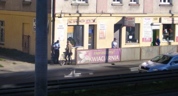 Strażnik miejski wypisuje mandat rowerzystce.